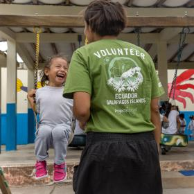 During volunteer work abroad with children in Ecuador a young child swings on the playground while a volunteer supervises